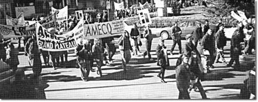 Le 29 octobre 1999, Yvan Noé Girouard et Raymond Gagnon brandissent bien haut la bannière de l'AMECQ devant les bureaux du ministre de la Solidarité sociale, André Boisclair, dans le cadre d'une manifestation pour la reconnaissance de l'action communautaire autonome.